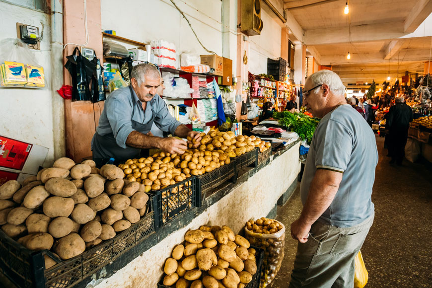 In a market, a potato salesman offers new potatoes to an older male customer