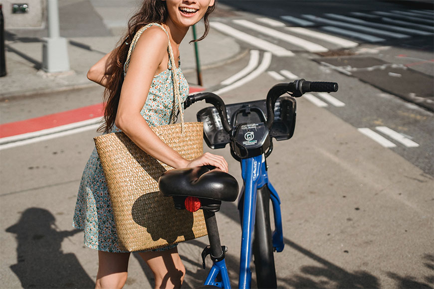 Smiling cyclist poses for a photo while steering her bicycle