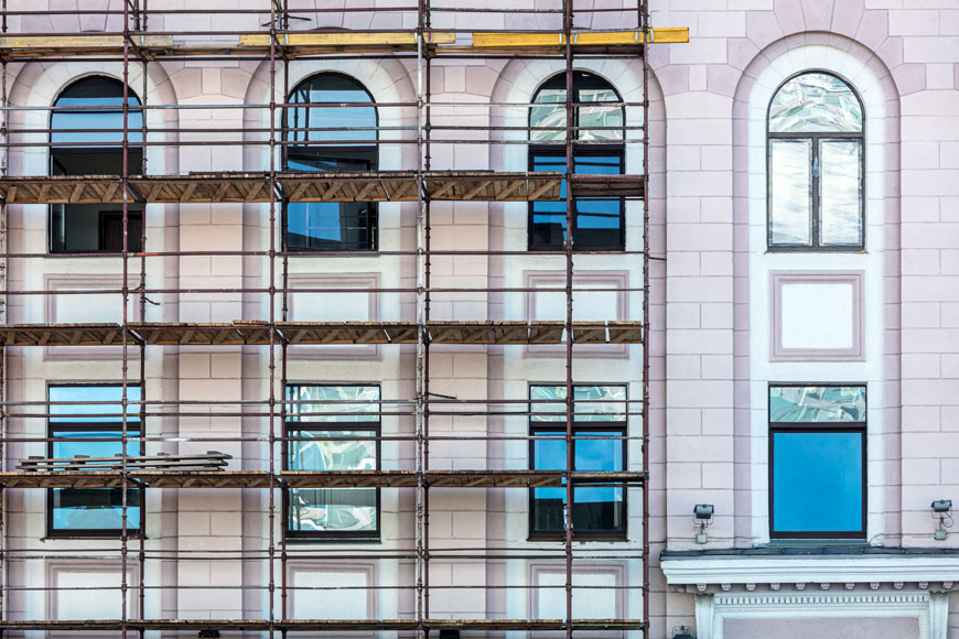 A pink stone building with windows reflecting blue sky has a framework of scaffolds during historic rehabilitation