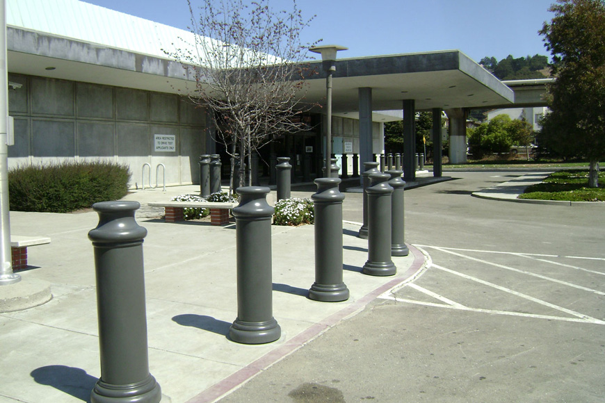 Grey, columnar post covers with curved caps and bases shape a perimeter around a low building
