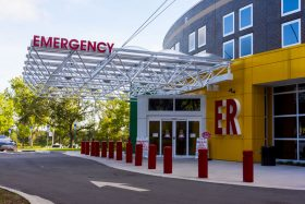 Bright red bollards protect the entrance to a hospital emergency room
