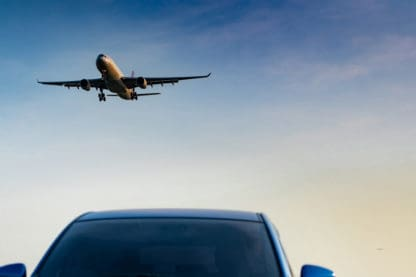 A plane takes off above the windshield of a blue car parked at an airport