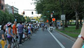"""A line of people as """"human bollards"""" stand between a cycle lane and traffic and cheer riders on"""