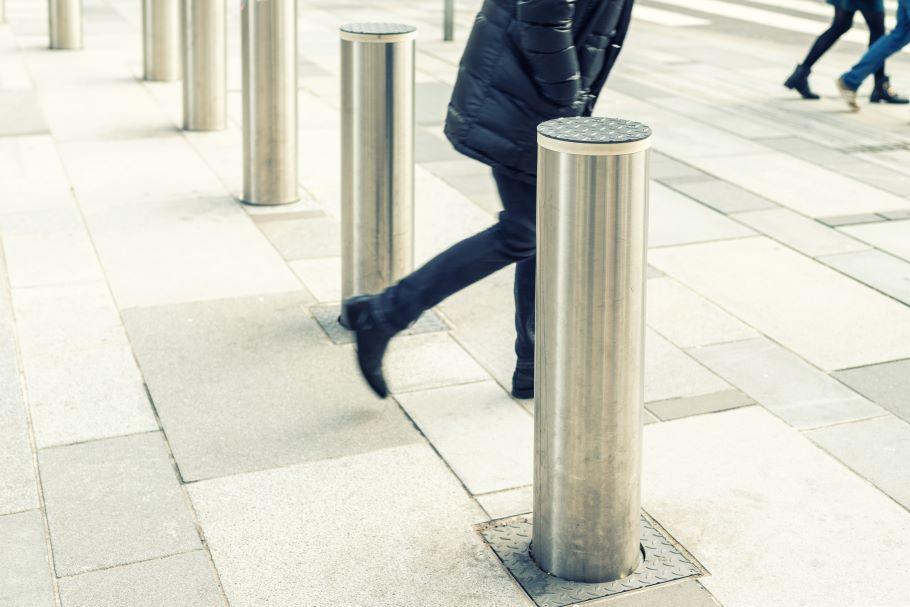 A pedestrian walks past a bollard