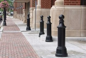 Large black cannon bollards protect the vehicle entrance of a red brick building