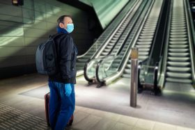 A man in a blue paper surgical mask stands near an escalator with a bollard before it.