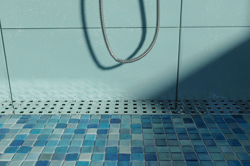 A shower with blue walls, mosaic tile floor in shades of blue, and a stainless steel channel grate with small square holes
