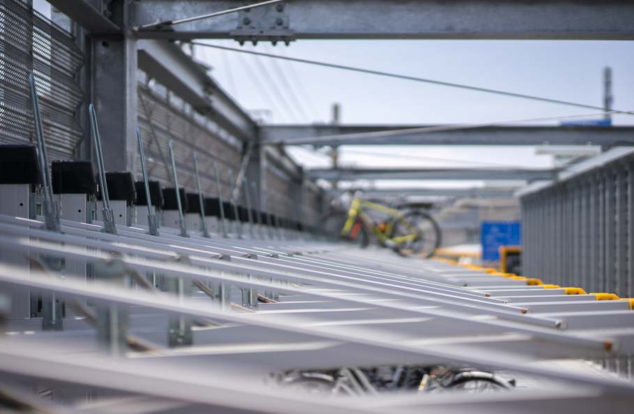 A shot of an industrial bike rack of two levels with one bike up and one down