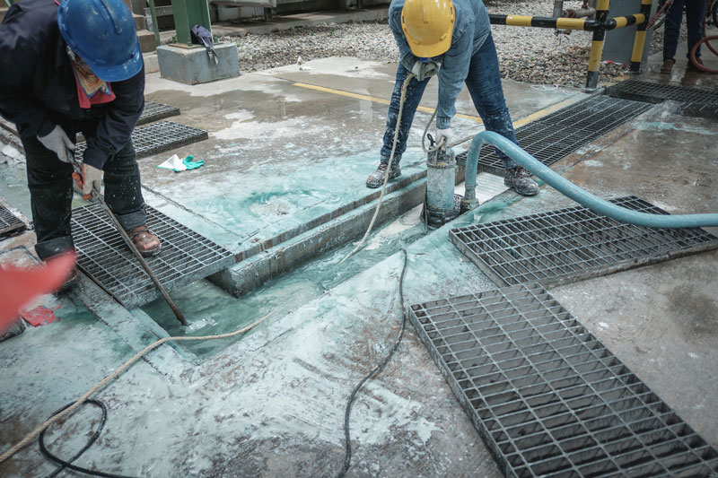 Two workers stoop over a wide channel full of turquoise liquid, grates removed, sump pump placed inside