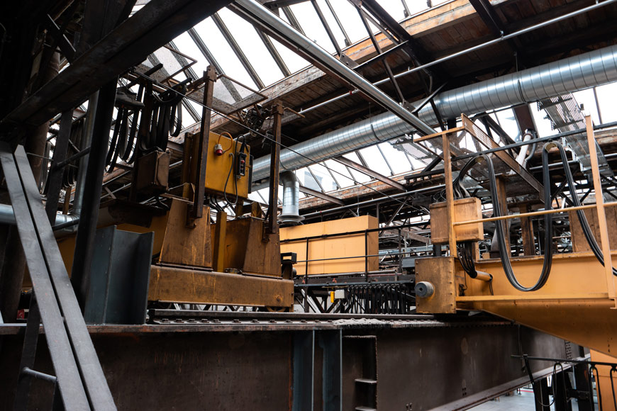 A heavy yellow machine sits atop a platform with raised rails in an abandoned factory.