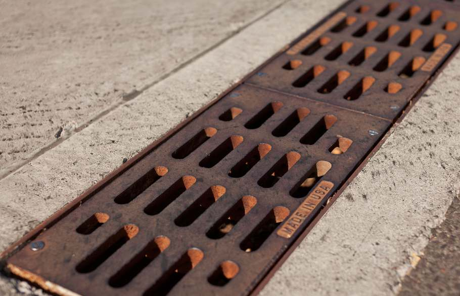 A cast iron trench grate with horizontal slots and a red iron oxide patina