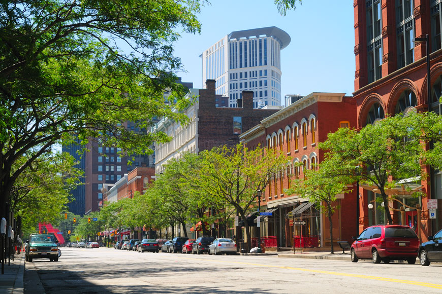 A tree-lined street in front of brick buildings in downtown Cleveland