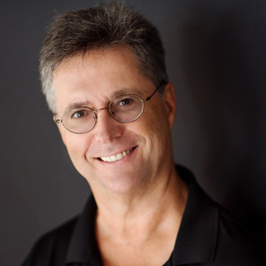 A head shot of a smiling man in glasses looking at the camera