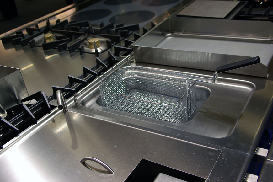 A gleaming new commercial kitchen has a deep fryer, warming box, and grill made of 316 steel