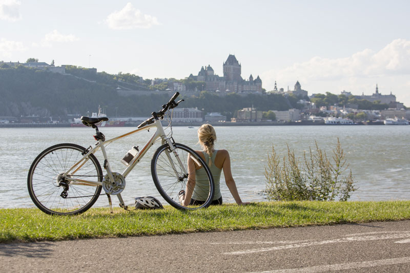 A woman sits beside her bike gazing at Quebec City.