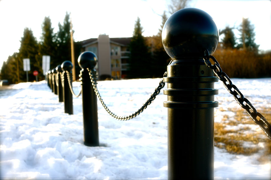 A line of dark bollards stand in the snow, connected with draping chains