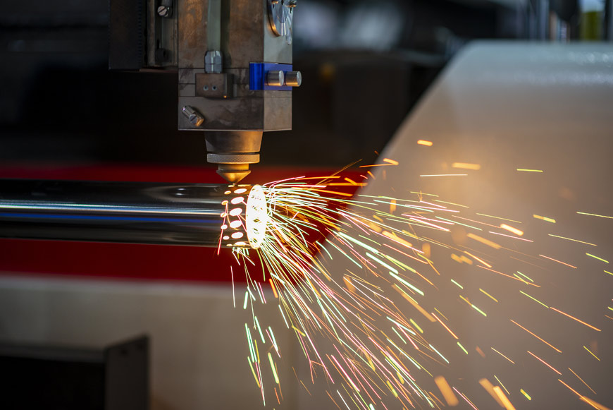 A piece of stainless steel pipe is laser cut using a cnc machine