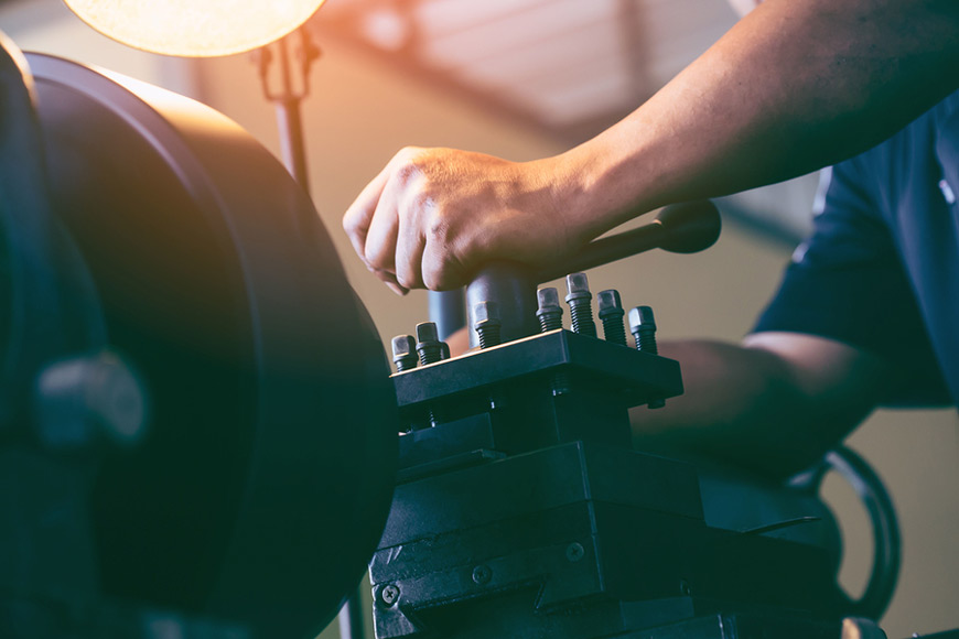 A worker uses a lathe grinder in a metal shop
