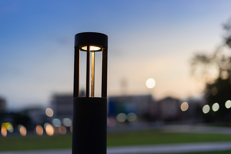 A lit bollard on a pathway at dusk