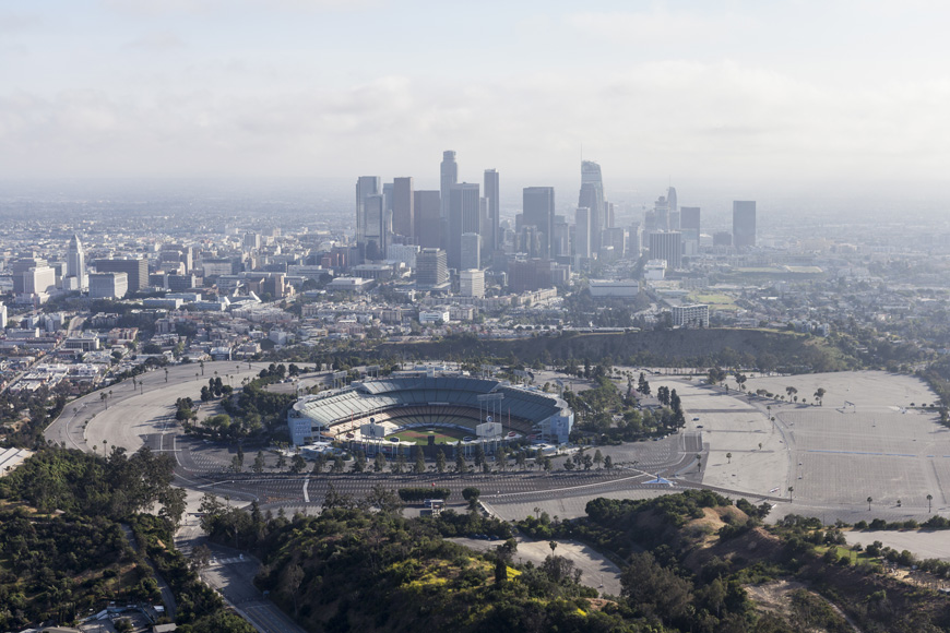 Arial picture of Dodger Stadium surrounded by a huge parking lot and smoggy city skyline