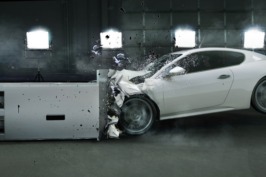 A high-speed crash test in a facility crumples the front of a grey passenger vehicle
