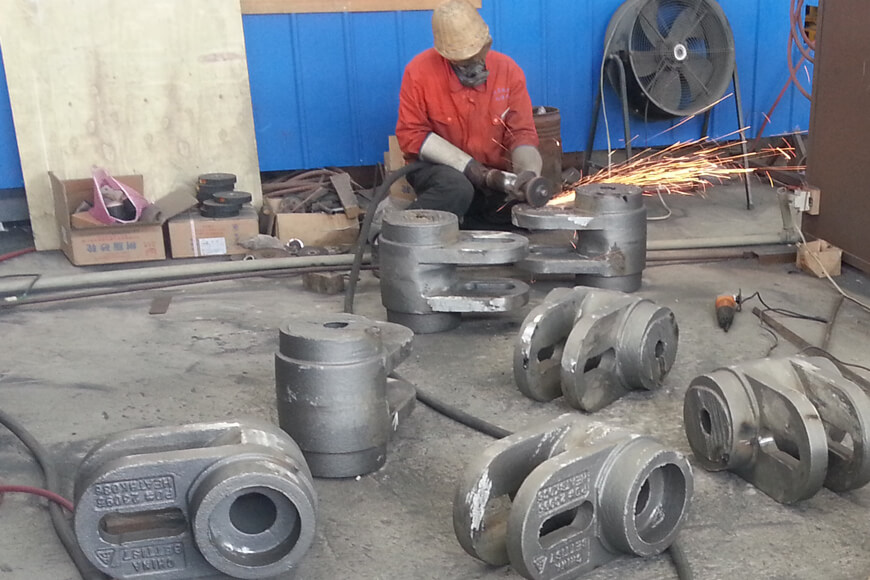 A foundry worker uses an abrasive grinder to remove flashing and other imperfections from a casting