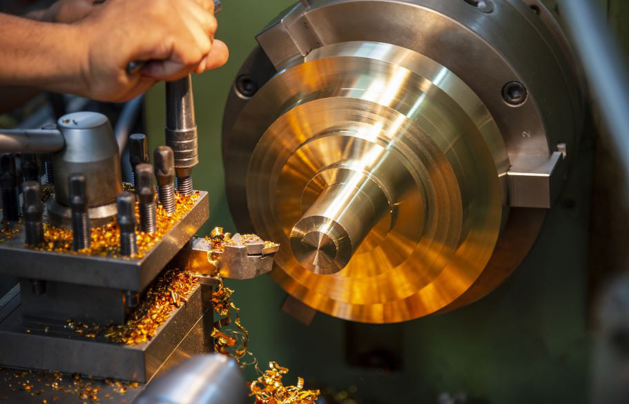 A worker runs a lathe that removes excess metal through machining