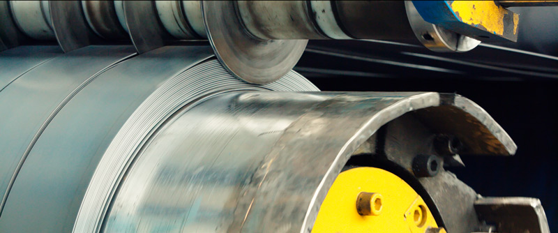 A large machine cuts a sheet of steel into strips and spins them onto a spool