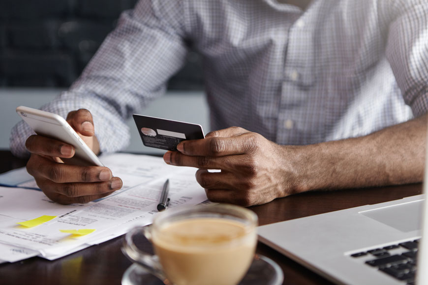 A businessman uses a credit card to place an online order with his phone