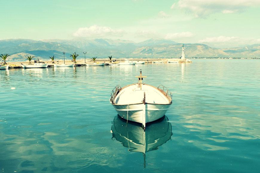 A small white fishing boat comes into a Greek marina on an aquamarine sea
