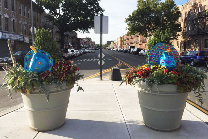 Martello bollard stands between concrete planters filled with plants and street art