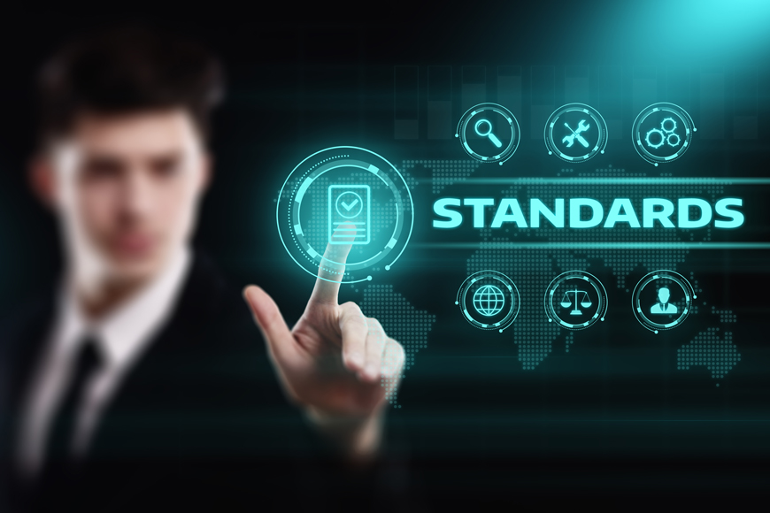 A man stands behind the word standards which is surrounded by icons suggesting process and manufacturing