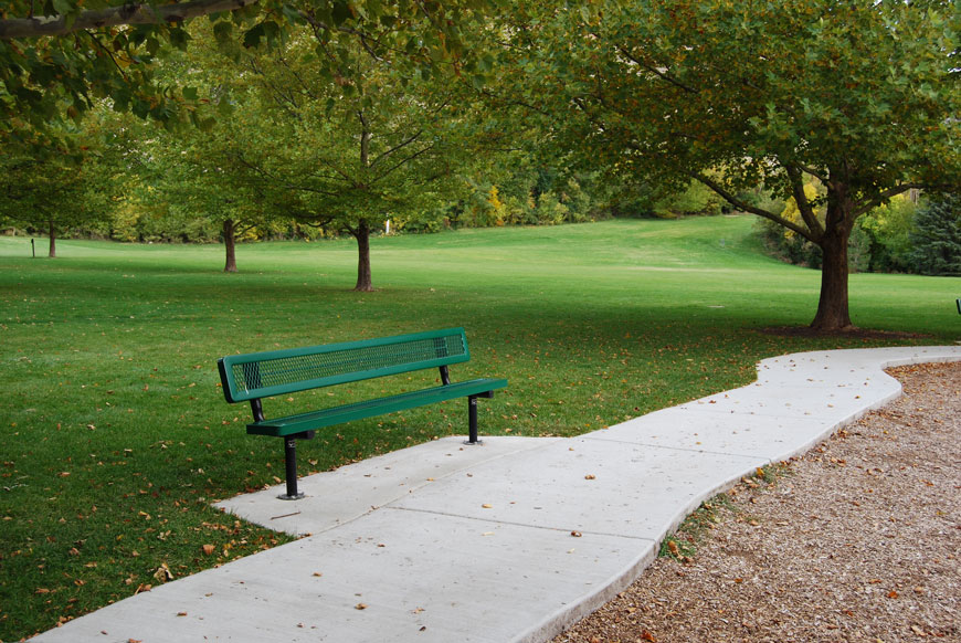 Bench made of green metal in a grid pattern sits beside sidewalk in a grassy park.