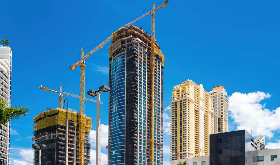Several cranes work on adjacent skyscrapers. The sky behind is blue. A yellow completed skyscraper sits in the background.