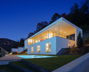 A long white rectangular house glows at sunset, a pool in front of it