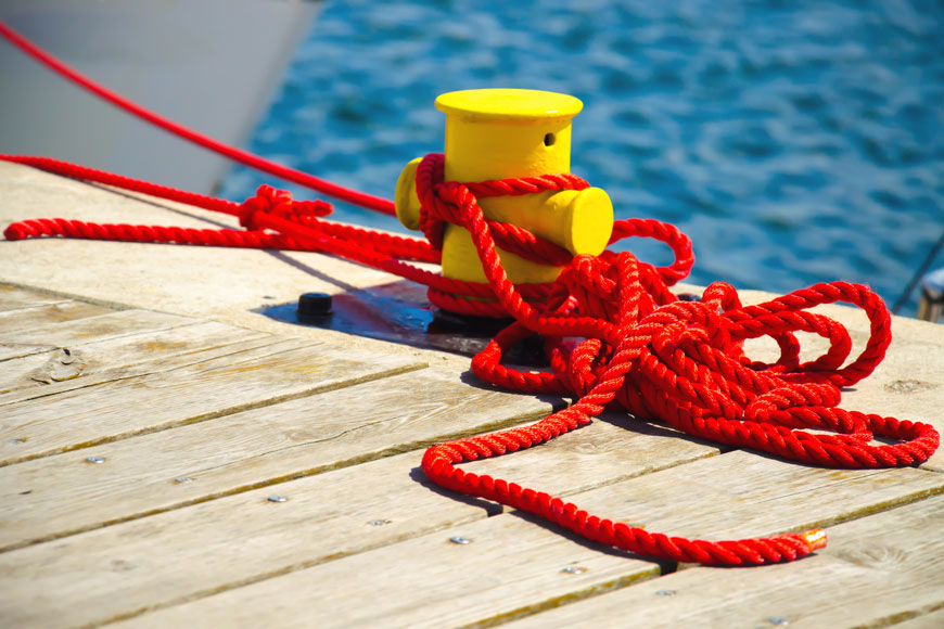 A short yellow mooring bollard is lashed with vibrant red rope beside a choppy sea