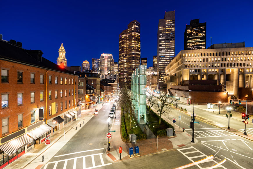 A nighttime photograph of a street with a median with trees and public art in Boston