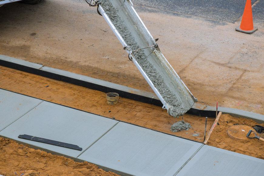 A concrete truck dumps wet cement over a rebar grid