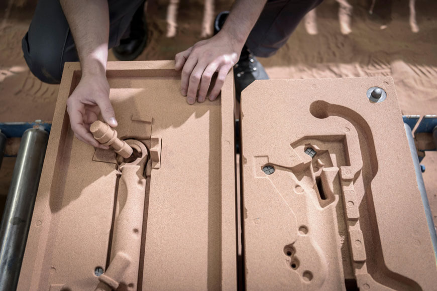 A foundry worker inserting cores into a no-bake sand mold