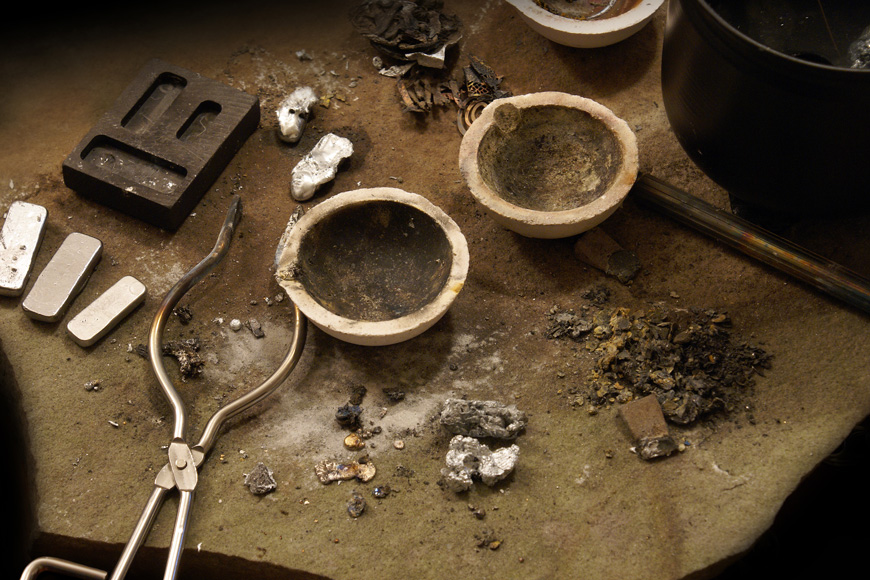 nonferrous metallurgist leaves silver ingots and gold nuggets beside crucibles and molds