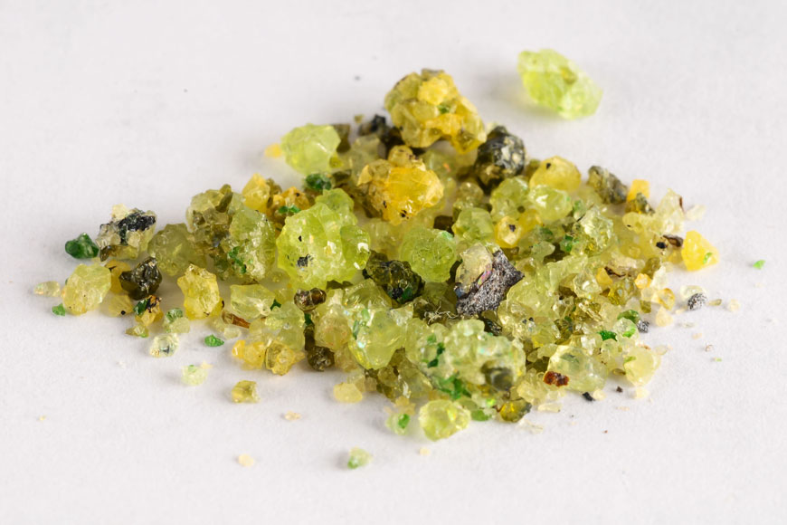 A pile of different sized green and yellow olivine crystals sits on a plain background