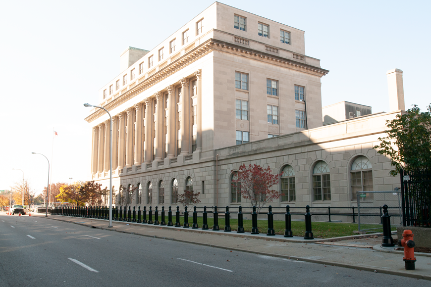 A large stone building with classic columns and impost blocks is enhanced with cannon bollards