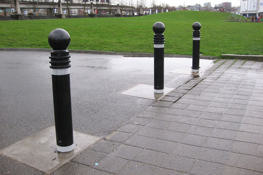 Bollards wrapped in reflective tape block a path beside a sloping green space