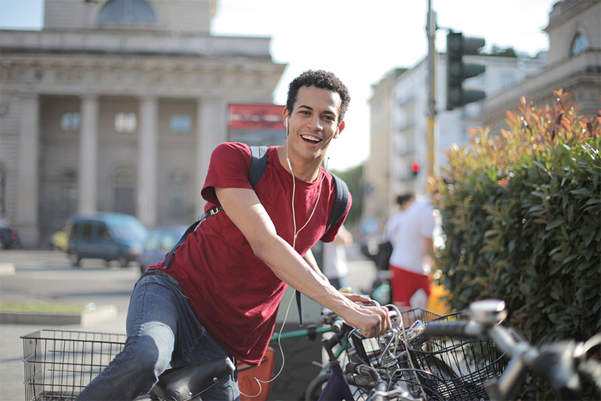 A young male happily cycling while listening to music about to park his bike