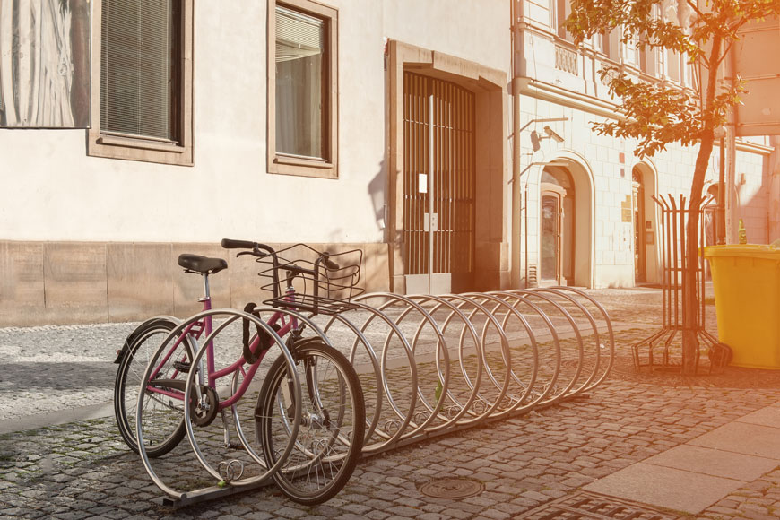 Early morning on European street: a single pink bike is locked to a spiral silver rack.
