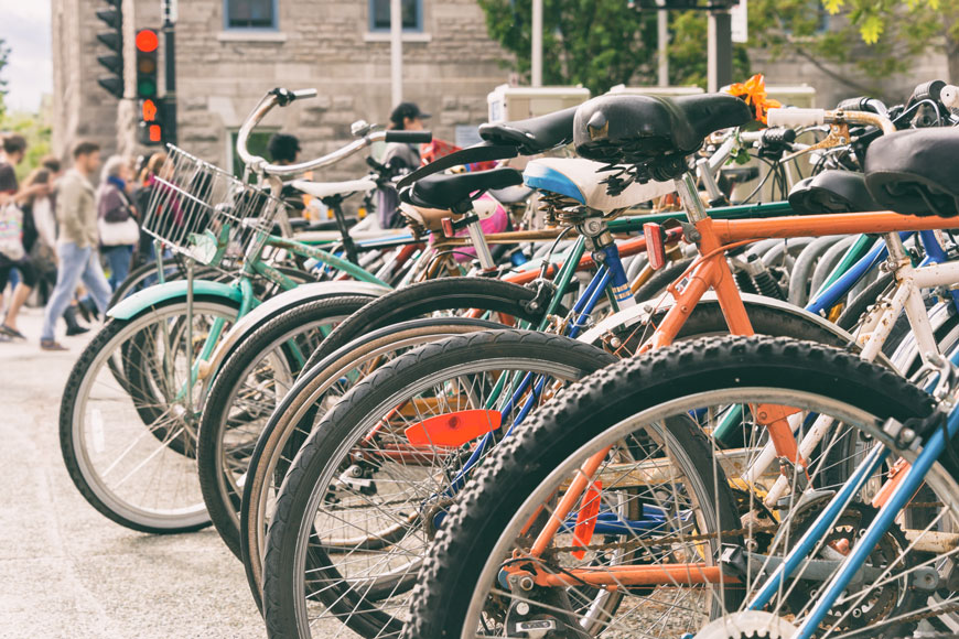 A cluster of bikes are parked outside of a university building in Montreal