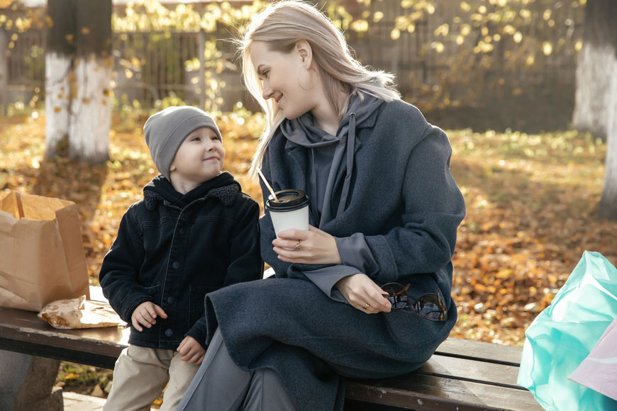 A mom and child sit on a backless park bench sharing a snack with their parcels spread around them.