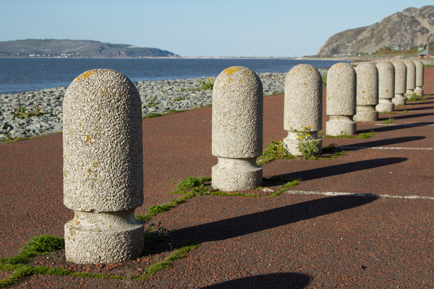 Numerous rounded concrete bollards in a line at a parking lot facing the ocean