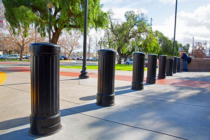 black bollards along sidewalk near parking lot