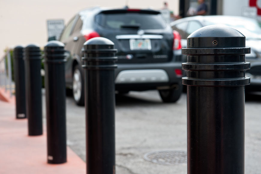 Ring-topped black bollards in the foreground, blurred cars in background